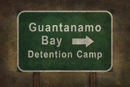 Guantanamo Bay detention camp road sign with directional arrow, illustration with distressed ominous background